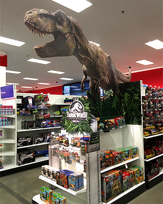 A giant cardboard T.rex juts out of a display in a Target store