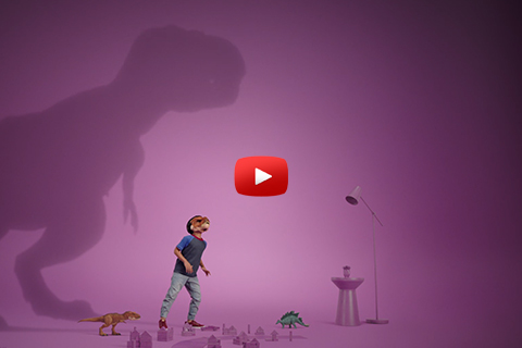 A little boy wearing a dinosaur mask roars while a shadow of a T.rex looms behind