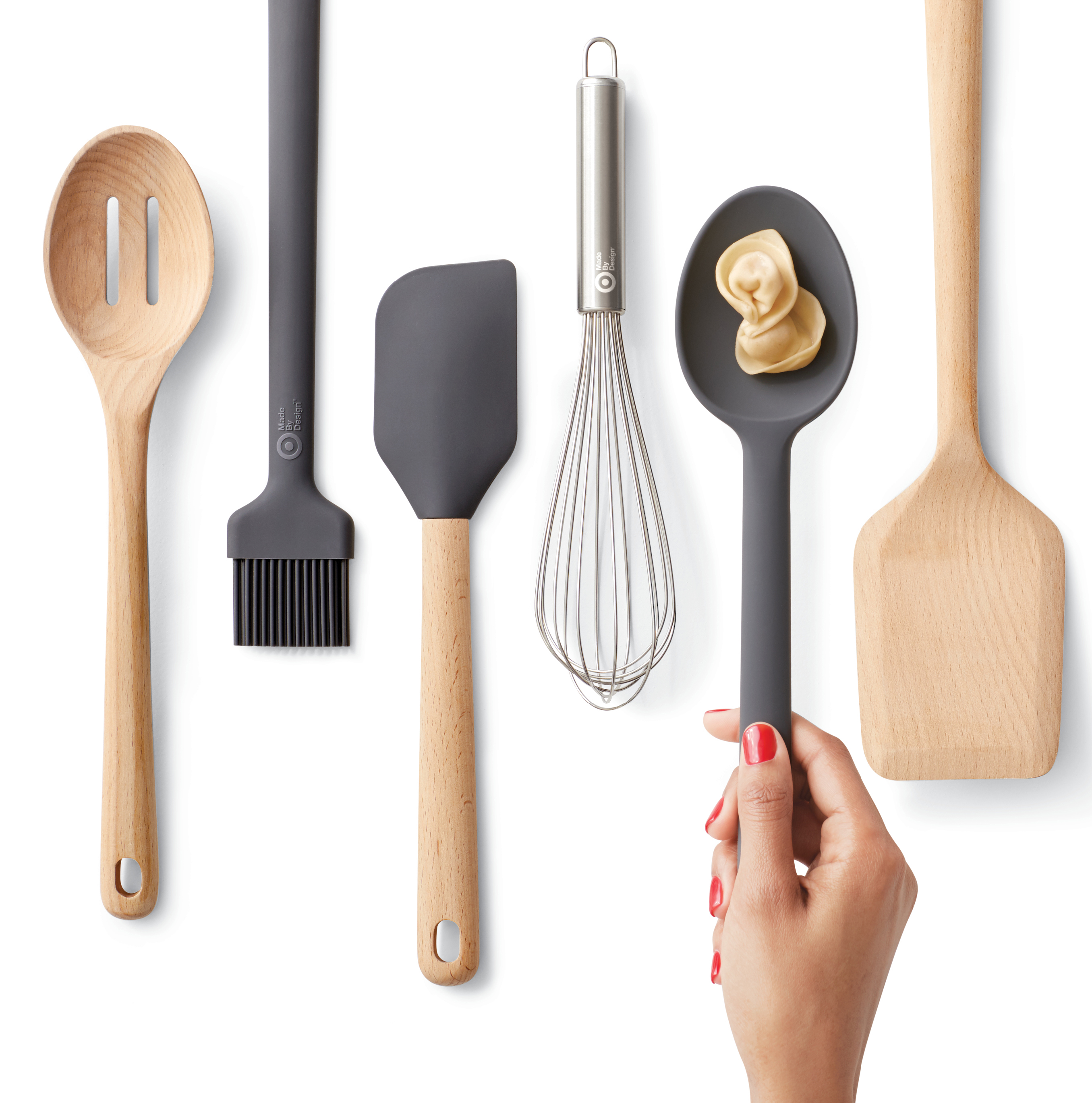A mix of plastic and wooden kitchen utensils, including slotted and regular spoons, basting brush, spatula and whisk