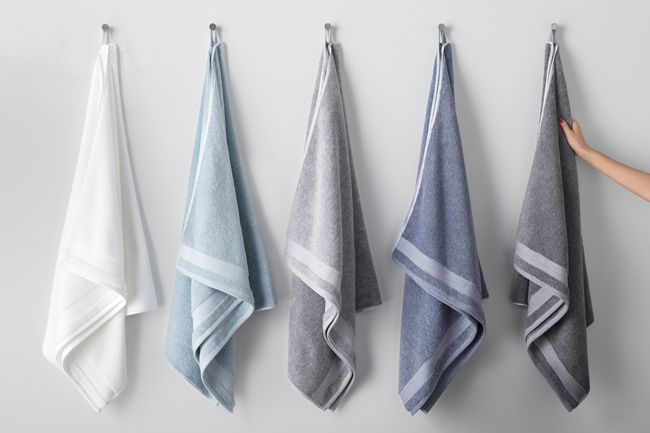 Five towels in white and shades of blue and grey hang from loops in a row