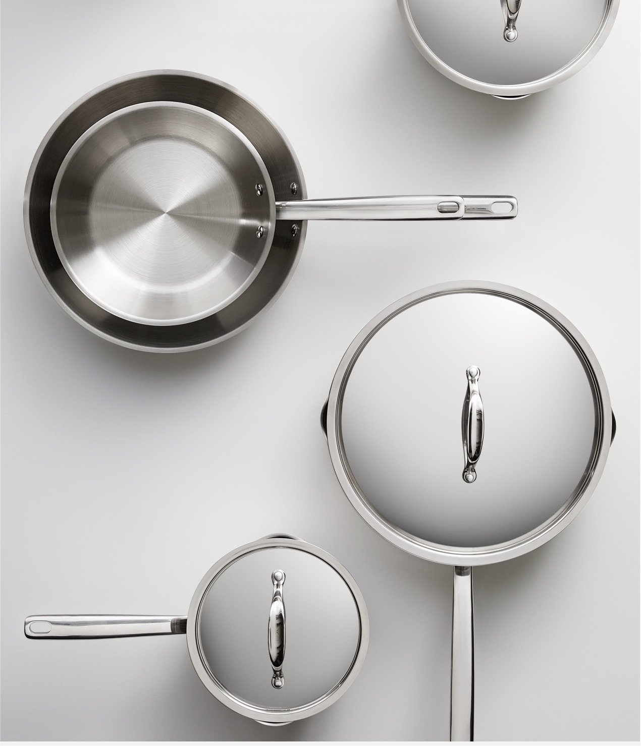 A variety of covered and uncovered stainless steel cookware
