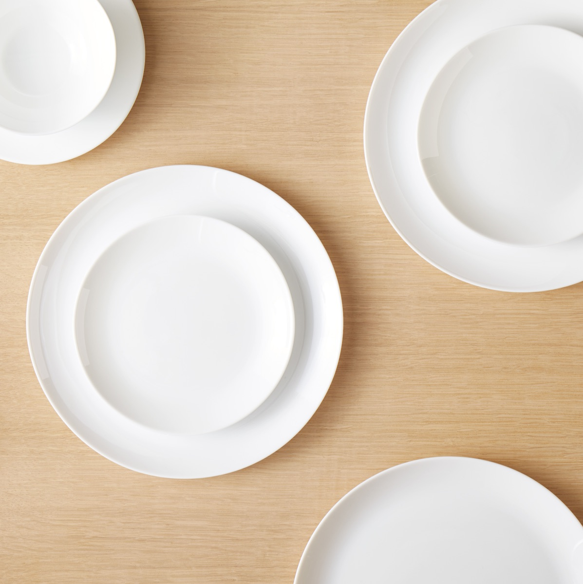 White, round dinner plates with white bowls stacked on top