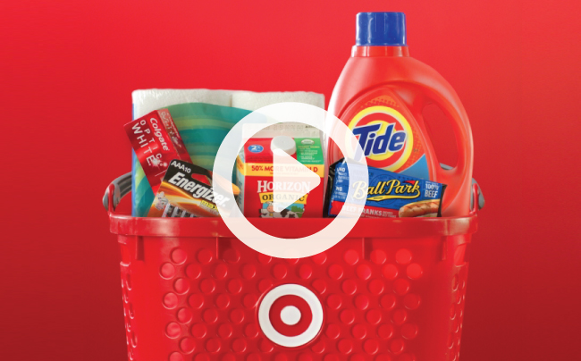 A red Target basket brimming with Tide, paper towels, toothpaste, milk, batteries and hot dogs