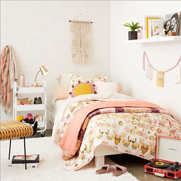 A globally-inspired dorm room, including blush bedding and accents, fringed accessories and pillows