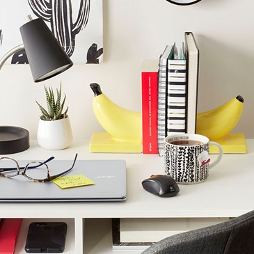 Close-up of a desk featuring banana book ends, black and white cactus print wall art, reading glasse