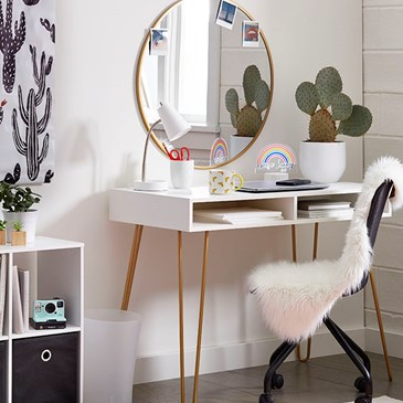 A desk doubles as a make-up table with blush accents, including a rug and fuzzy throw