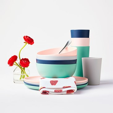 A stack of colorful plates, bowls and drinking glasses with a flower-print napkin and a few flower b