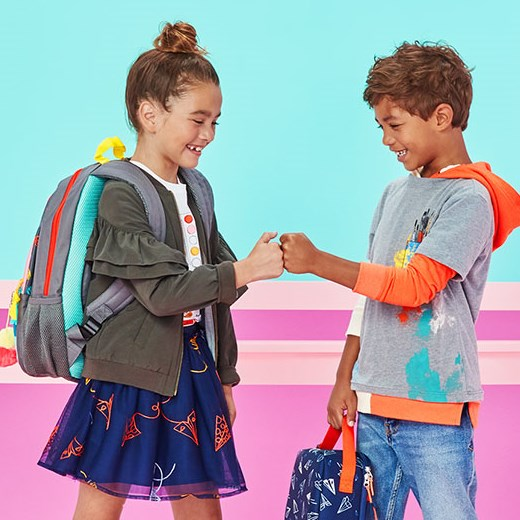 Girl and boy decked out in back-to-school outfits and backpacks