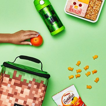 Lunch box, bento box and snacks on a green background