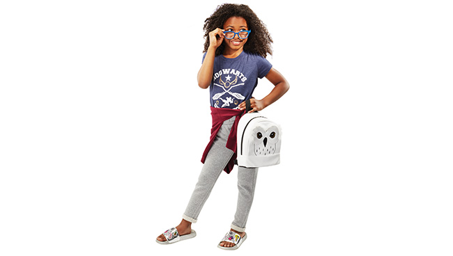 A young girl wears a blue Hogwarts shirt while carrying a backpack featuring a white owl