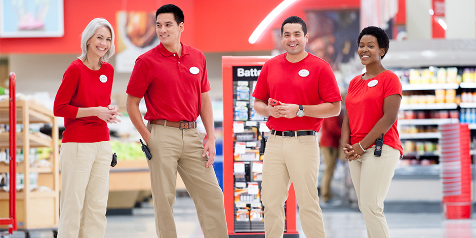 Four team members wearing red and khaki, standing in front of product displays in a store