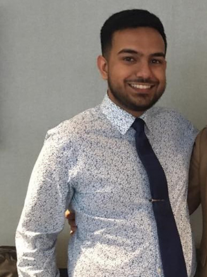 Karan wearing a dress shirt and tie, standing in his workspace