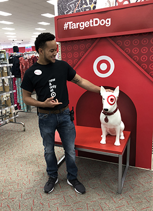 LJ standing next to and pointing at a Bullseye the Dog statue in a store