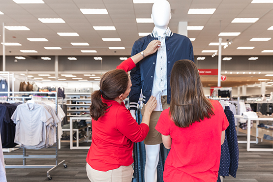Two team members style a mannequin