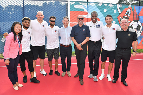 Influencers and players stand together on the court in front of the mural