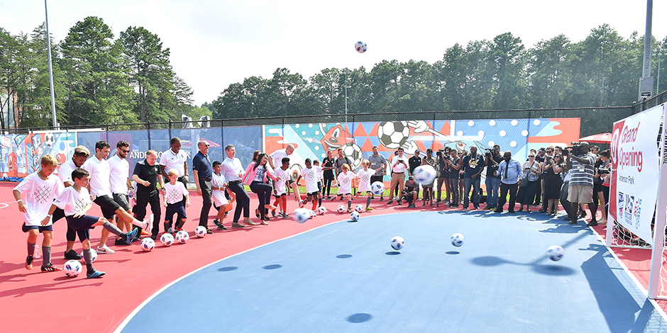 Kids and pro players perform the ceremonial first kick at their new play space in Atlanta