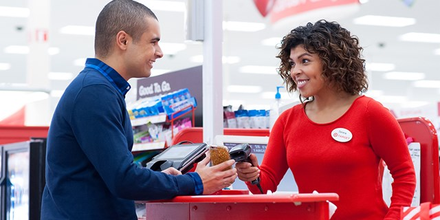 A team member scans a guest's smartphone at the checkout