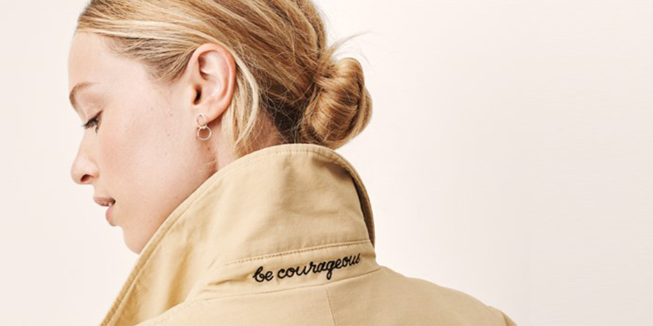 A woman wearing a tan trench with 'be courageous' embroidered on the collar