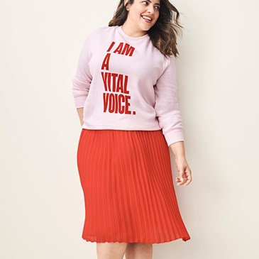 A model wearing a pink sweatshirt with red orange text and a knee-length orange pleated skirt