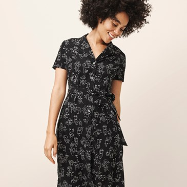 A model wears a black, short sleeve dress with white floral print