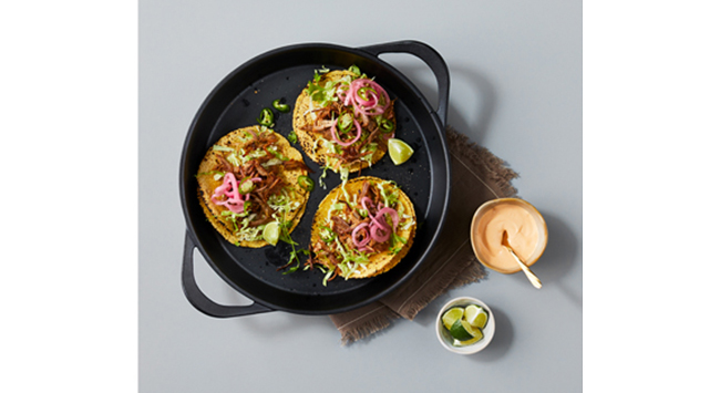 A cast iron pan filled with three tostadas