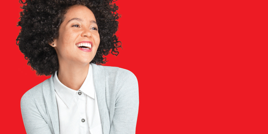 A smiling woman in a grey sweater and white button-down smiles against a red background