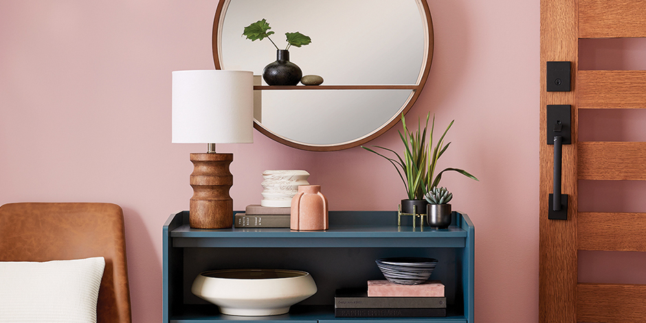 Modern furniture and decor are shown against a pink-hued wall