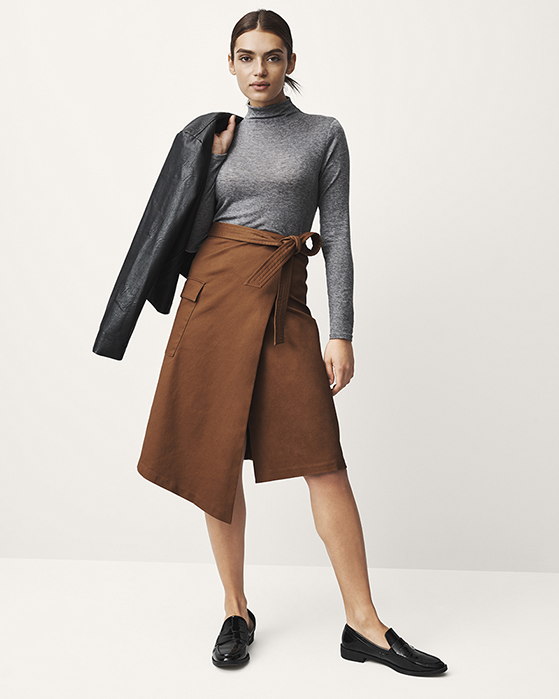 A female model in a gray top, black jacket and tan skirt