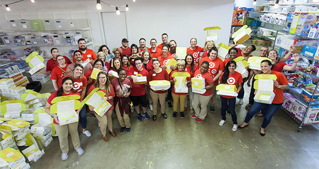group of volunteers in red shirts hold birthday kit boxes