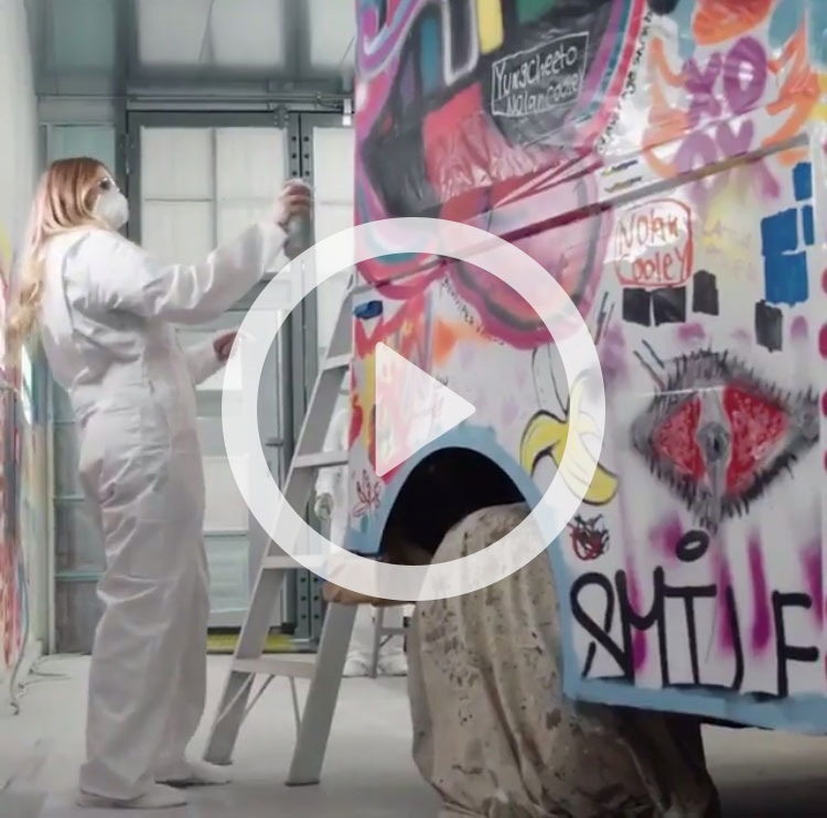 A young woman spray paints an ice cream truck