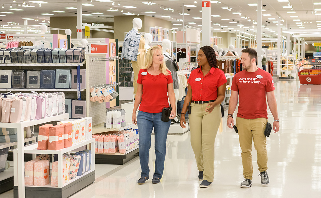 interior of a store aisle, three team members walking in red, denim and khaki
