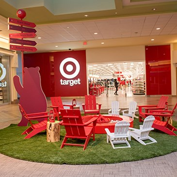 A circle of red and white lawn chairs around a fake Bullseye-shaped campfire outside the new store