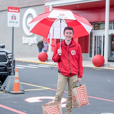 A Drive Up team member stands holding an umbrella and shopping bags