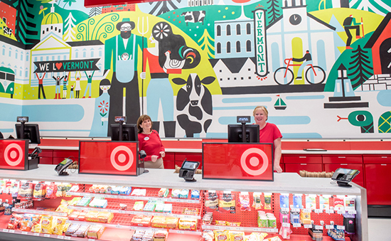 Two team members staff cash registers in front of a giant mural