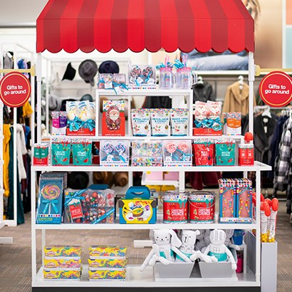 A display of colorful gifts displayed on a shelf with a red awning