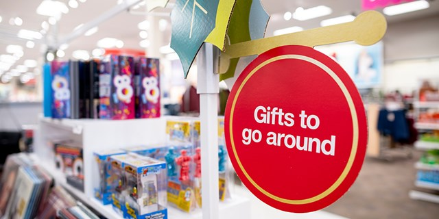 A red Gifts to go around sign with a variety of gifts in the background