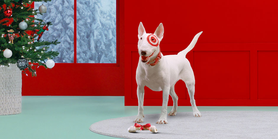 Bullseye the dog stands in front of a festive holiday background, with a bow-wrapped bone