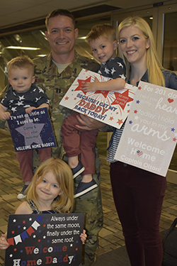 Emily and her family holding signs to welcome Jared home