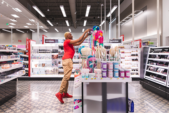 A team member arranges products on a curated display in the Beauty department