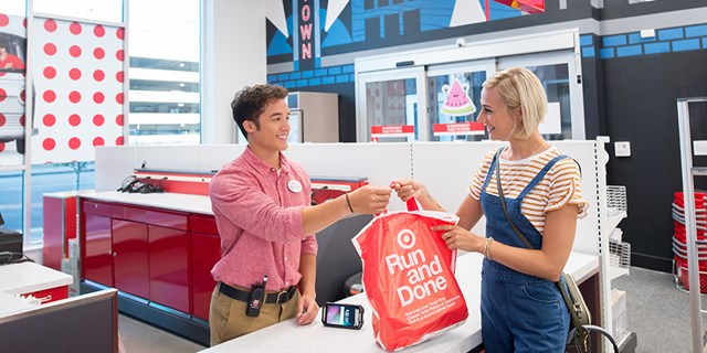 A team member hands a guest a bag with her Order Pickup order