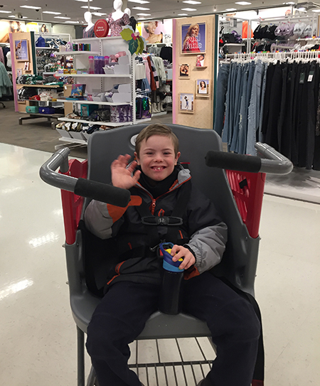 A boy sits in the seat of a Caroline's Cart, waving to the camera in a Target aisle