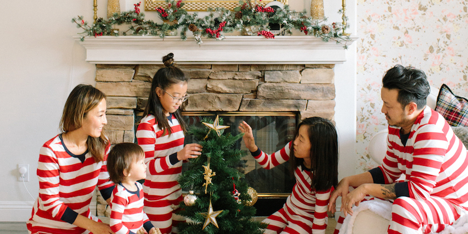 A family of five wearing matching red and white striped pajamas decorates a Christmas tree
