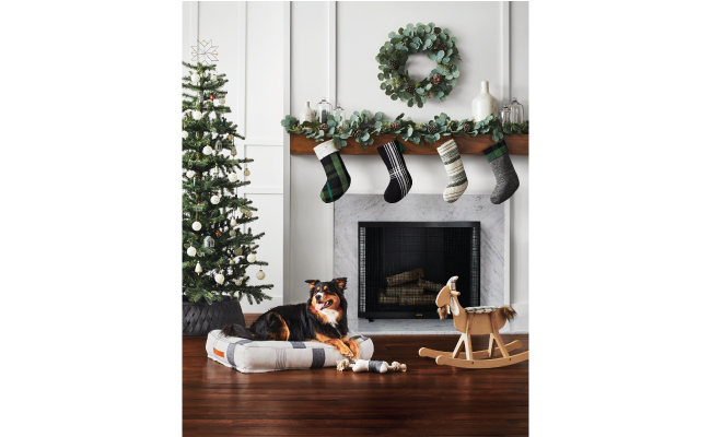 A white room is decorated with greenery, Christmas tree, and stockings above the mantle. A dog sits on a dog bed near a rocking goat.