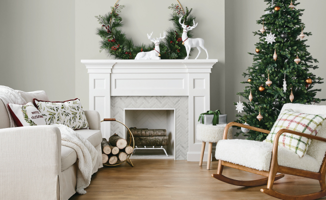 A white fireplace is decked in greenery and reindeer figures. A tree, couch and chair with festive throw pillows and a log holder are also shown.