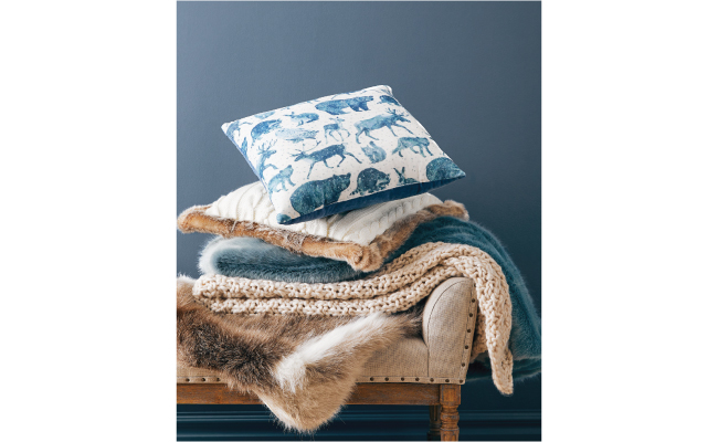 A blue and cream throw pillow featuring rustic animals sits atop a pile of cozy throws.