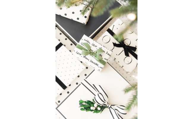 A variety of gifts wrapped in cream paper with black and green accents.