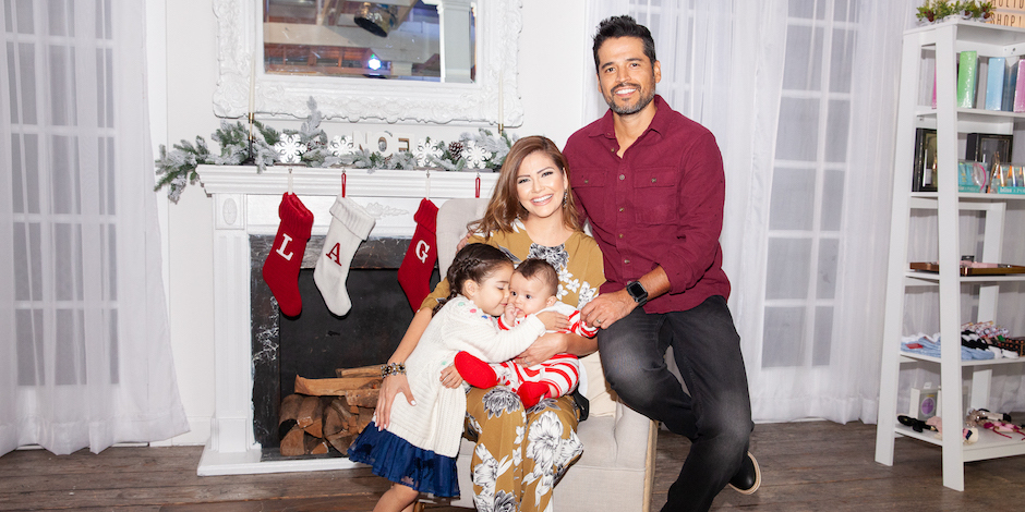 Ana Patricia and her husband and kids sit together in front of their fireplace