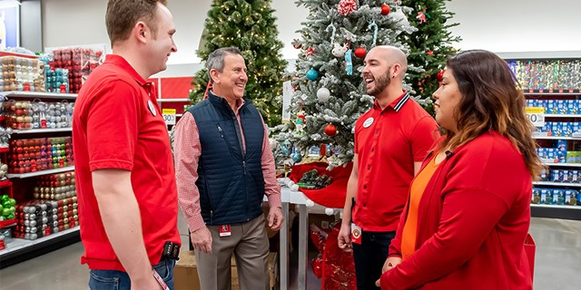 Brian Cornell stands with three team members in front of displays with Christmas trees and ornaments