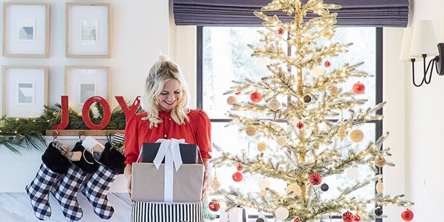 Emily Henderson holds a stack of wrapped gifts near a decorated Christmas tree and mantle