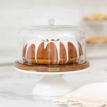 A covered cake stand with an iced bundt cake